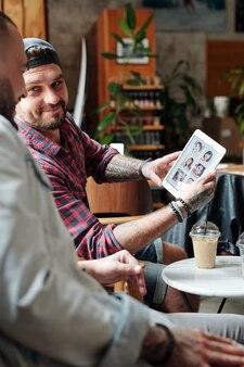 Conteúdo jovem barbudo mostrando fotos de mulheres para um amigo enquanto escolhe uma garota por meio de um aplicativo de namoro online