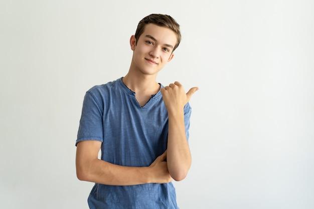 Conteúdo jovem bonito na camiseta azul apontando de lado