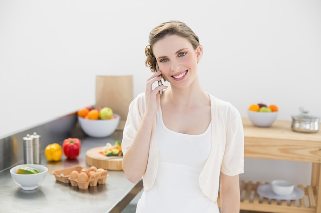 Conteúdo jovem mulher apertada enquanto está de pé na cozinha