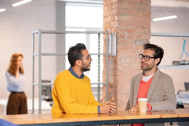 Conteúdo, jovens colegas multiétnicos em trajes casuais, em pé no balcão de um escritório de espaço aberto e falando sobre um novo projeto