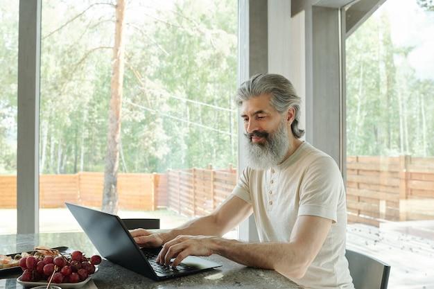 Conteúdo moderno homem de barba cinza sentado no balcão da cozinha e usando o laptop em uma casa de campo