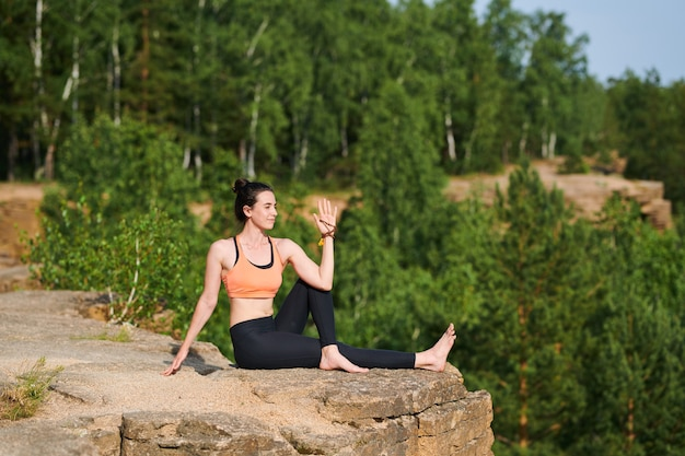 Conteúdo mulher bonita em roupas esportivas sentada em uma pedreira e girando o corpo enquanto fortalece o núcleo da coluna ao ar livre