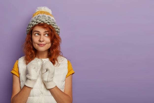 Conteúdo, mulher caucasiana adorável usa chapéu branco de inverno, luvas e sonha com boas férias durante as férias