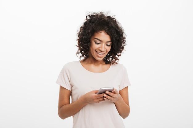 Conteúdo mulher sorridente com penteado afro, digitando a mensagem de texto ou usando a internet no smartphone, isolado sobre a parede branca