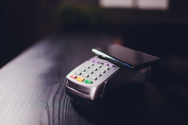Conteúdo satisfeito homem barbudo bonito em fones de ouvido dando cartão de crédito para garçonete enquanto pagava a conta no café.
