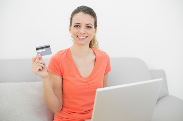 Conteúdo sorridente mulher mostrando seu cartão de crédito, mantendo seu notebook