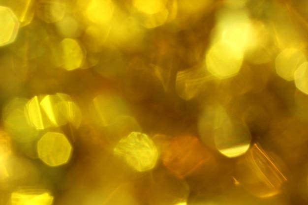 Contexto abstrato do borrão obscuro do bokeh dourado.