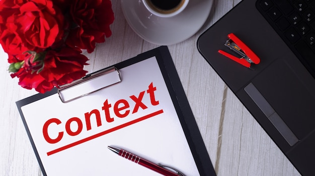 Contexto é escrito em vermelho em um bloco de notas branco perto de um laptop, café, rosas vermelhas e uma caneta.