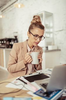 Continue trabalhando. mulher bonita concentrada segurando a xícara de café com as duas mãos e olhando para o laptop dela.