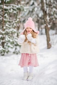 Conto de fadas menina bonita em uma neve de chapéu-de-rosa branco casaco de pele nas mãos