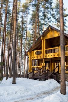 Conto de inverno. casa de campo finlandesa em uma bela floresta de neve. casa de campo de madeira na floresta de pinheiros de inverno, o telhado está coberto de neve, casa de férias. natureza do norte