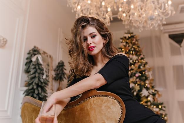 Contra a árvore decorada de natal linda mulher de cabelos compridos com bela figura misteriosamente parece
