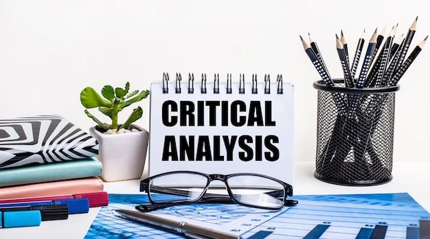 Contra a parede de um esquema azul e uma parede branca, lápis pretos em um suporte, uma flor, diários e um caderno com a inscrição análise crítica