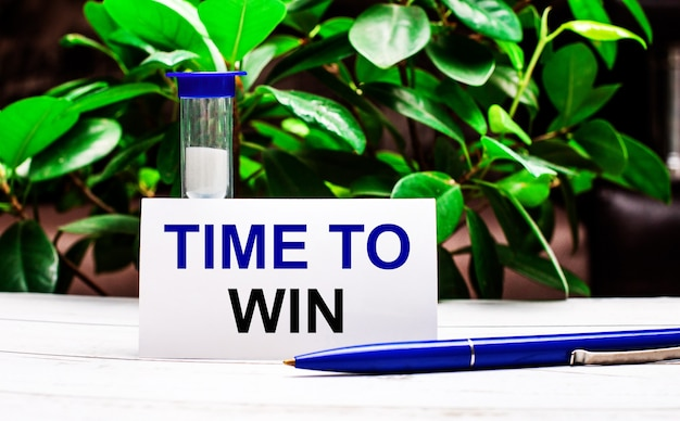 Contra a superfície das folhas verdes da planta, há uma caneta sobre a mesa, uma ampulheta e um cartão com a inscrição tempo de vencer