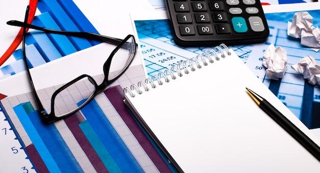 Contra a superfície de documentos e gráficos - uma caneta com um caderno, uma calculadora e óculos em armações pretas