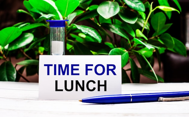 Contra o fundo das folhas verdes da planta, há uma caneta sobre a mesa, uma ampulheta e um cartão com a inscrição hora do almoço