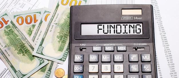 Contra o fundo de dinheiro e documentos está uma calculadora preta com o texto financiamento no placar. conceito de negócios