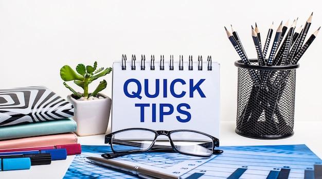 Contra o fundo de um esquema azul e uma parede branca, lápis pretos em um suporte, uma flor, diários e um caderno com a inscrição quick tips.