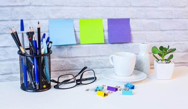 Contra o fundo de uma parede de tijolos claros, em uma mesa clara, há diários, um despertador branco