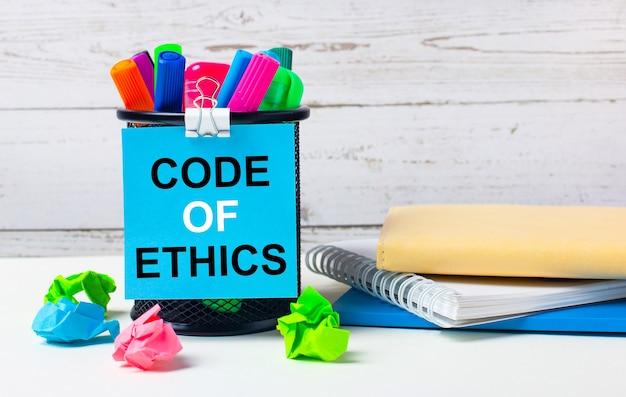 Contra um fundo claro de parede de madeira, um vidro com marcadores coloridos, folhas de papel brilhante amassado e uma folha de papel azul com a inscrição código de ética.