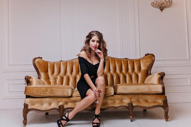 Contra uma parede branca, linda mulher de cabelos castanhos, em um vestido de cocktail preto e com uma taça de champanhe nas mãos, olha apaixonadamente