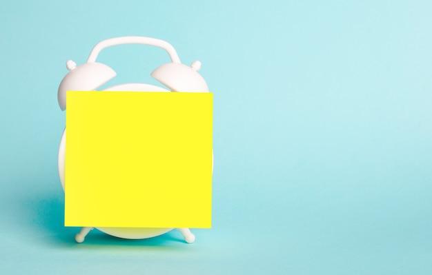Contra uma superfície azul clara, há um despertador branco com um adesivo amarelo de nota nele