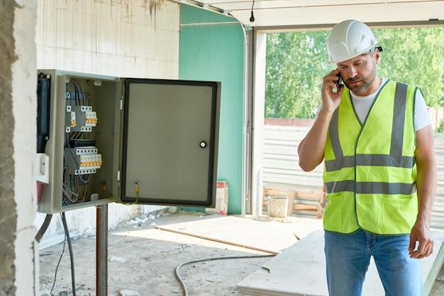 Contramestre da construção falando por telefone