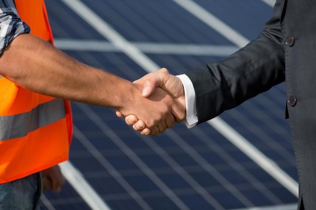 Contramestre e homem de negócios que agitam as mãos na estação da energia solar.