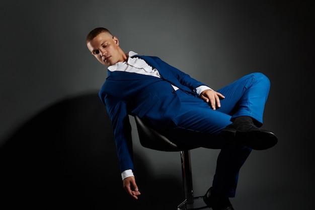Contraste o retrato de um empresário de homem em um terno de negócio caro em um fundo escuro. empresário bem sucedido gerente emocional, posando de gestos com as mãos no preto
