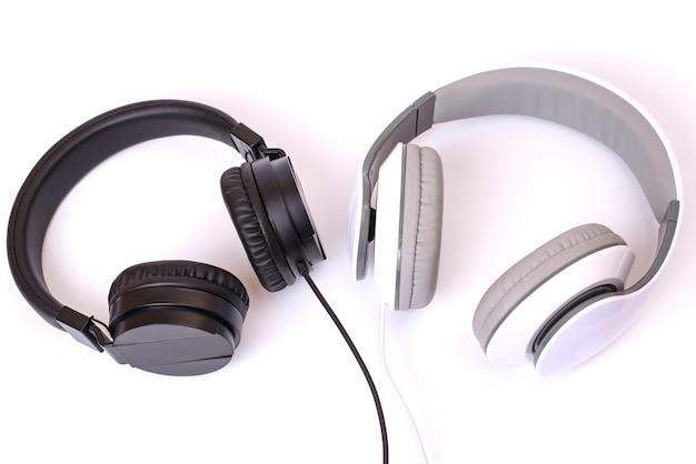 Contraste oposto ao conceito de estilo confortável e confortável. acima acima da cabeça acima, veja a foto de um par de fones de ouvido claros e escuros com cabos isolados no espaço de cópia de parede