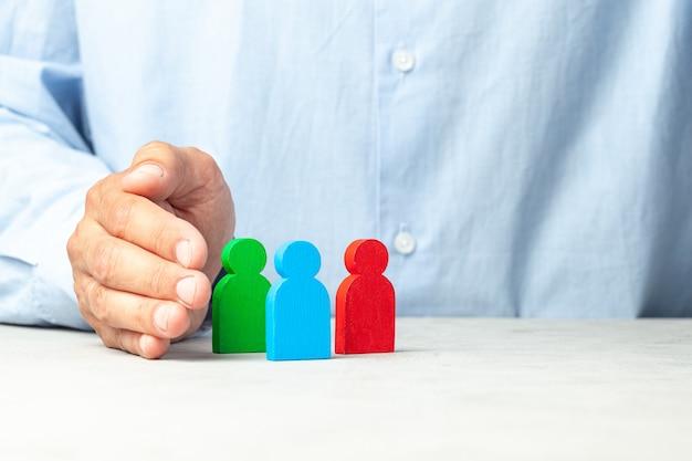 Contratação de funcionários como escolher um bom líder de funcionários homem de camisa segura figuras nas mãos
