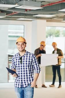 Contratante jovem bonito positivo com tablet digital dentro do prédio em construção
