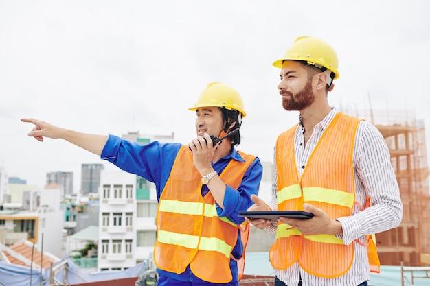 Contratante vietnamita sorridente falando no walkie-talkie e apontando para longe ao lado do engenheiro-chefe com um tablet digital nas mãos