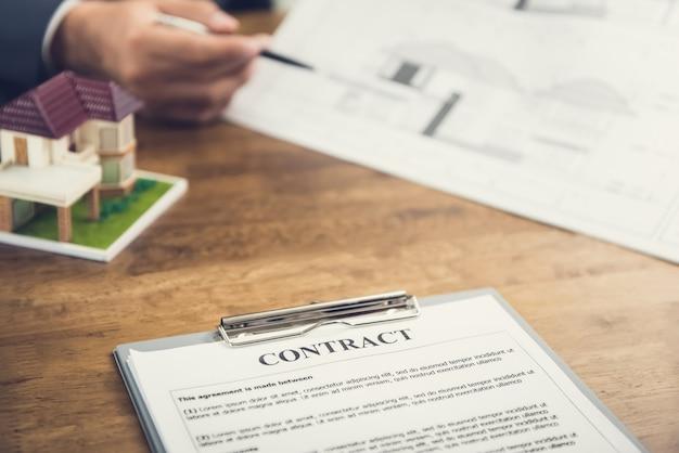 Contrato contrato papel e casa modelo em cima da mesa com borrão mão do empresário revendo blueprint no fundo