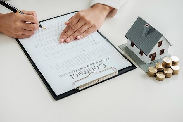 Contrato de assinatura da mulher de negócio para comprar a casa, seguro ou empréstimo imobiliário na tabela.