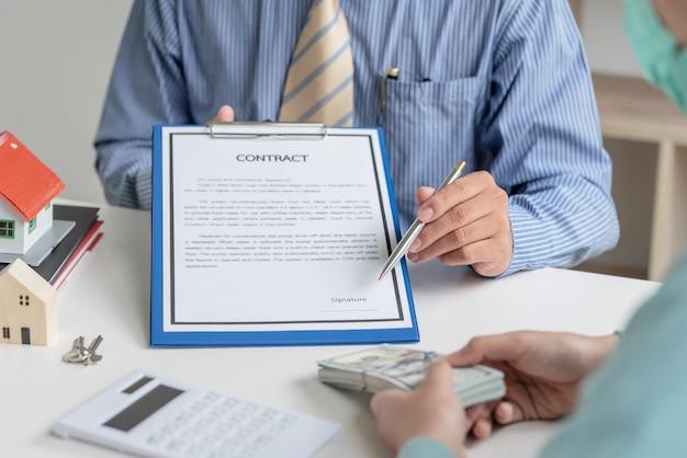Contrato de assinatura de contrato de compra e venda de casa no escritório.