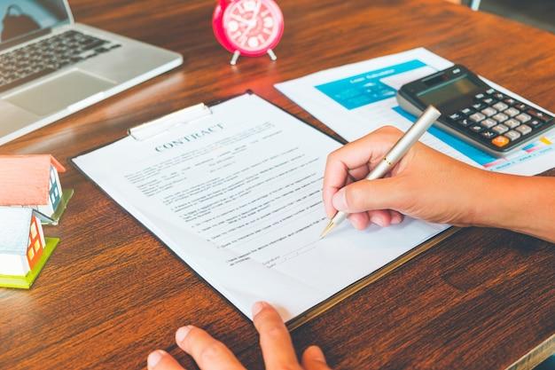Contrato de casa, o homem assina um contrato para comprar uma casa com um agente imobiliário