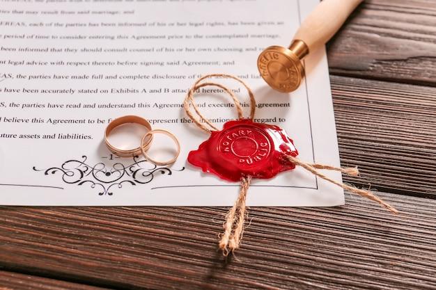 Contrato de casamento com selo de cera e alianças na mesa