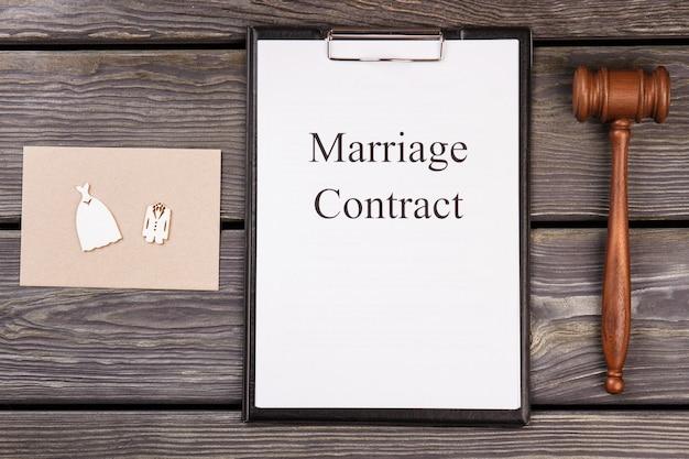 Contrato de casamento e martelo de madeira na mesa.