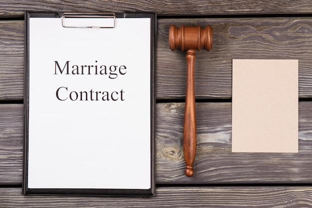 Contrato de casamento e martelo de madeira.