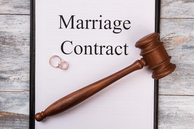 Contrato de casamento na área de transferência. alianças de casamento e vista superior do martelo.