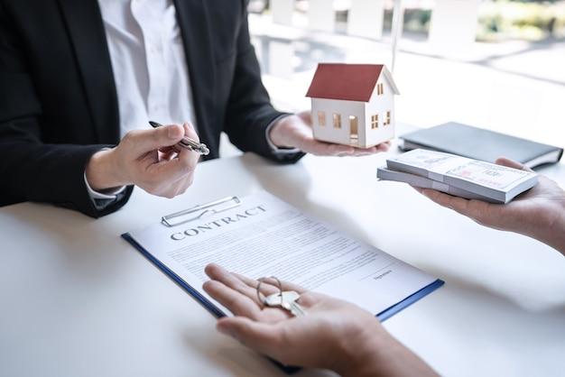 Contrato de compra e venda para compra de casa, agente imobiliário está apresentando empréstimo hipotecário e entrega de chaves ao cliente após a assinatura do contrato de compra de casa com formulário de pedido de propriedade aprovado.