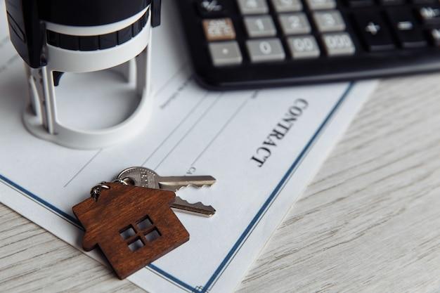 Contrato de empréstimo hipotecário com chaveiro em forma de casa de madeira