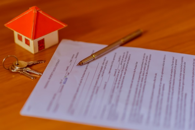 Contrato de hipoteca para venda de imóveis com uma caneta e chaves de casa