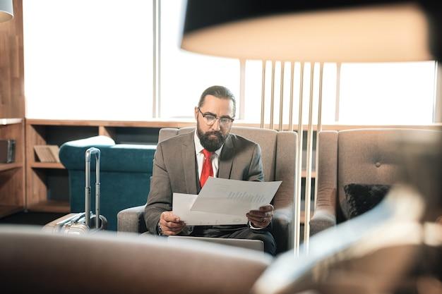 Contrato de leitura. homem de negócios maduro, de cabelo escuro e barbudo lendo contrato, sentado em uma poltrona confortável