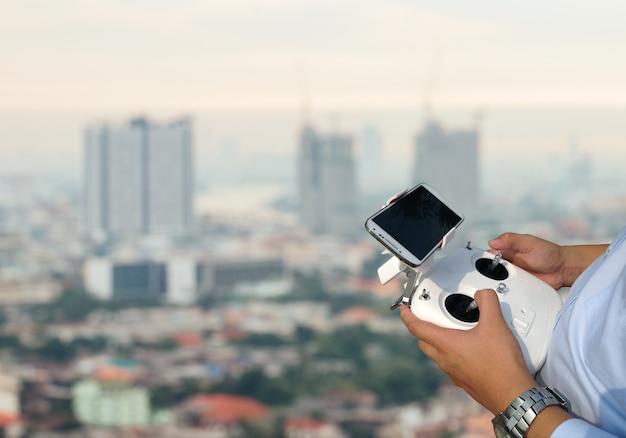 Controlador de drone no fundo da cidade
