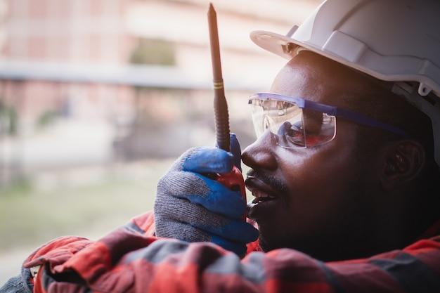 Controlador de engenharia do homem africano verificando, trabalhando com comunicação de rádio móvel ou walkie-talkie no sistema de sala na indústria