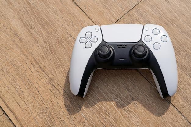 Controlador de jogo branco de próxima geração isolado em fundo de madeira. luz natural. foco seletivo.