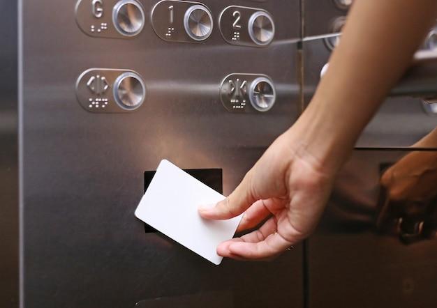 Controle de acesso de elevador, mão segurando um cartão-chave para desbloquear o elevador