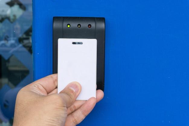 Controle de acesso de porta - jovem mulher segurando um cartão-chave para bloquear e destravar a porta
